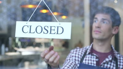 man-flipping-over-cafe-closed-sign