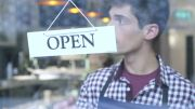 stock-footage-man-flipping-over-cafe-open-sign